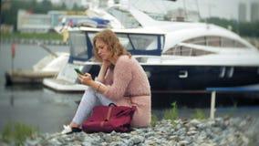 Una muchacha que usa un smartphone en la playa, el yate y la navegación en el puerto almacen de video