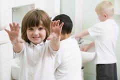 Una muchacha que visualiza sus manos en un cuarto de baño de la escuela Foto de archivo libre de regalías