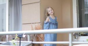 Una muchacha rubia agradable se está colocando en el balcón y está enviando un beso del aire almacen de metraje de vídeo