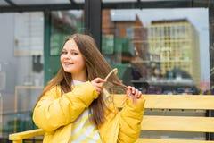 Una muchacha rubia de pelo largo, alegre se peina el pelo fotografía de archivo