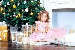 Una muchacha rubia dulce con los rizos en un vestido rosado se sienta en las decoraciones del Año Nuevo en la chimenea blanca y l Fotografía de archivo libre de regalías
