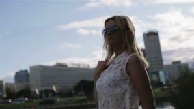Una muchacha rubia en gafas de sol que disfruta de la visión metrajes