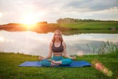 Una muchacha rubia hermosa está practicando yoga en el lago en la puesta del sol Primer Fotos de archivo