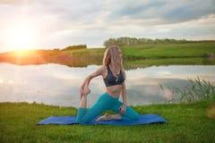 Una muchacha rubia hermosa está practicando yoga en el lago en la puesta del sol Primer Foto de archivo libre de regalías
