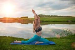 Una muchacha rubia hermosa está practicando yoga en el lago en la puesta del sol primer apoya una forma de vida sana Fotos de archivo