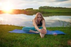 Una muchacha rubia hermosa está practicando yoga en el lago en la puesta del sol primer apoya una forma de vida sana Fotografía de archivo