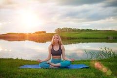 Una muchacha rubia hermosa está practicando yoga en la posición de loto respecto al lago en la puesta del sol primer apoya una fo Foto de archivo libre de regalías