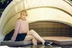 Una muchacha rubia joven del adolescente en la calle Muchacha que se sienta en el sofá rottan en restaurante Imagen de archivo libre de regalías