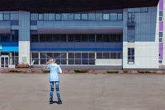 Una muchacha rubia joven en una chaqueta azul est? patinando sobre ruedas alrededor del cuadrado para los paseos y del resto en u imagen de archivo libre de regalías