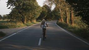Una muchacha rubia joven en pantalones en la bici retra que va abajo del camino en el campo almacen de video