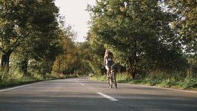 Una muchacha rubia joven en pantalones en la bici retra que va abajo del camino en el campo almacen de metraje de vídeo