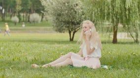 Una muchacha rubia joven está hablando en el teléfono en un parque de la ciudad que se sienta en la hierba metrajes