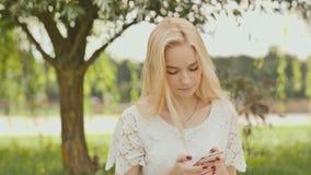 Una muchacha rubia joven está mecanografiando en el teléfono blanco en un parque de la ciudad almacen de metraje de vídeo
