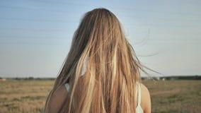 Una muchacha rubia joven se coloca con ella detrás que demuestra su pelo largo almacen de metraje de vídeo