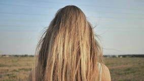 Una muchacha rubia joven se coloca con ella detrás que demuestra su pelo largo almacen de video