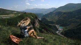 Una muchacha rubia joven se sienta en la hierba en un fondo de montañas con una mochila y toma las imágenes de las montañas almacen de video