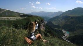 Una muchacha rubia joven se sienta en la hierba en un fondo de montañas con una mochila y toma las imágenes de las montañas almacen de metraje de vídeo