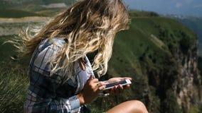 Una muchacha rubia joven se sienta en la hierba en un fondo de montañas con una mochila y toma las imágenes de las montañas metrajes