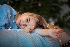 Una muchacha rubia joven sonríe misterioso y miente en la cama en un suéter azul foto de archivo