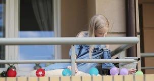 Una muchacha rubia linda en un vestido se sienta en el balcón y los juegos con las luces del día de fiesta almacen de video