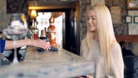 Una muchacha rubia recibe su té y paga él almacen de metraje de vídeo