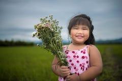 Una muchacha sana que sostiene el ramo de la flor en el campo con el smil Foto de archivo libre de regalías