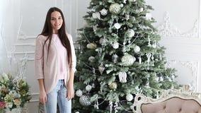 Una muchacha se coloca cerca de un árbol de navidad Año Nuevo, día de fiesta, vacaciones almacen de metraje de vídeo