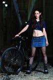 Una muchacha se coloca cerca de una bici interior abandonada Foto de archivo libre de regalías