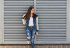 Una muchacha se coloca cerca de una cerca de persianas Imagenes de archivo