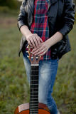 Una muchacha se coloca con una guitarra sin jugar, secuencias en descanso, la Imagen de archivo libre de regalías