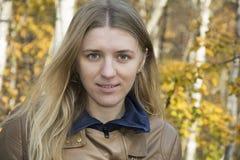 Una muchacha se coloca en bosque del otoño Fotografía de archivo