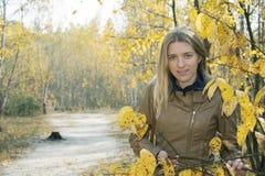 Una muchacha se coloca en bosque del otoño cerca de un camino Fotos de archivo libres de regalías