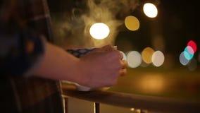 Una muchacha se coloca en el balcón con una taza de té, mirando el fondo urbano hermoso almacen de video