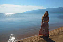 Una muchacha se coloca en la orilla del lago Baikal foto de archivo