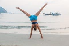 Una muchacha se coloca en sus manos en una playa arenosa, disfruta de vida con el franco Imagen de archivo libre de regalías