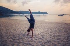 Una muchacha se coloca en sus manos en una playa arenosa, disfruta de vida con el franco Fotografía de archivo