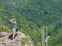 Una muchacha se coloca en un acantilado contra la perspectiva de bosque verde imagenes de archivo