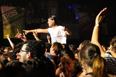 Una muchacha se coloca sobre la muchedumbre en un concierto en la discoteca del Razzmatazz Fotos de archivo