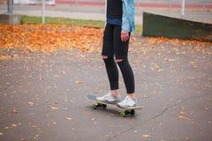 Una muchacha se está colocando con sus dos piernas en un monopatín en un parque del patín Fotografía de archivo libre de regalías