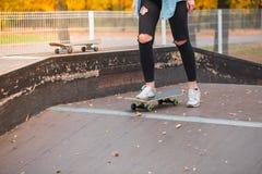Una muchacha se está colocando con un pie en un monopatín en un parque del patín Fotos de archivo libres de regalías