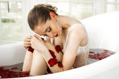 Una muchacha se está sentando en el cuarto de baño con los pétalos color de rosa Un baño de la salud con las rosas imagenes de archivo