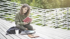 Una muchacha se está sentando en las escaleras que lee un libro al aire libre Imágenes de archivo libres de regalías