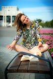 Una muchacha se está sentando en un banco en una actitud del loto Foto de archivo libre de regalías