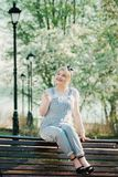Una muchacha se está sentando en un banco con una puntilla de flores de cerezo adentro foto de archivo libre de regalías