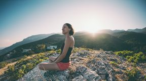 Una muchacha se está sentando encima de una montaña y de una sonrisa Foto de archivo