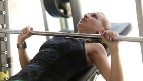 Una muchacha se resuelve en el gimnasio que levanta los músculos del pecho del entrenamiento del barbell metrajes