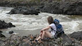 Una muchacha se sienta en el banco de un río de la montaña almacen de metraje de vídeo