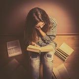 Una muchacha se sienta en el piso y la lectura de un libro endereza el pelo con su cierre de la mano encima del tono retro Imagen de archivo
