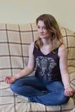 Una muchacha se sienta en el sofá en una actitud del loto Fotografía de archivo libre de regalías