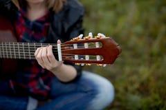 Una muchacha se sienta en la hierba con jugar de la guitarra, poniendo su mano Fotografía de archivo